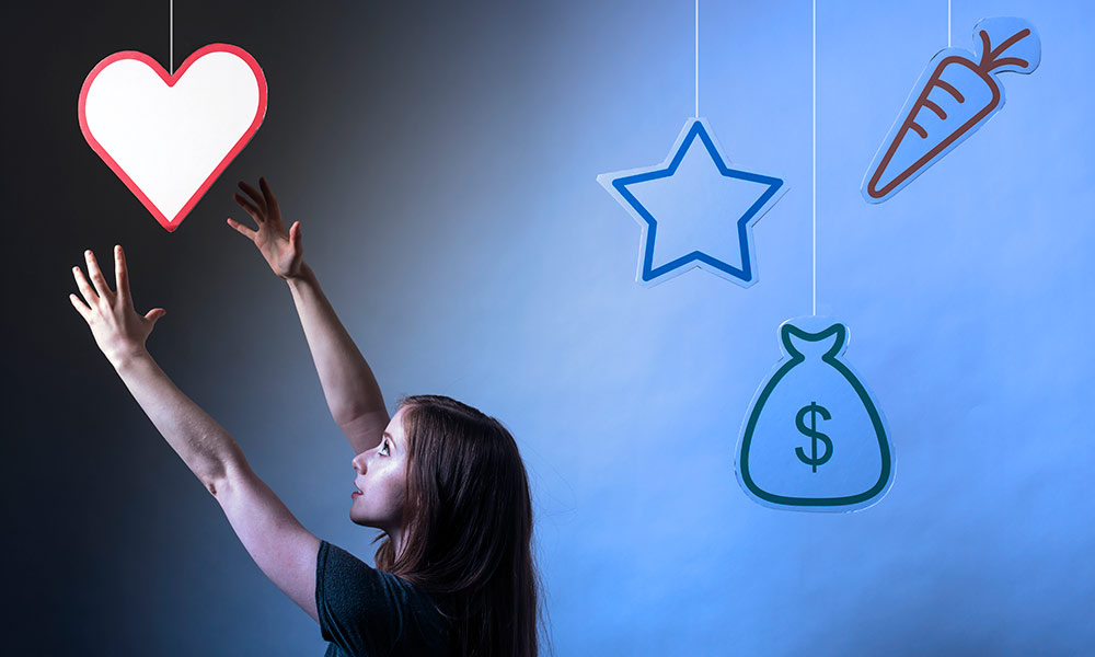 young woman reaching for a paper heart, ignoring a star, money and carrot