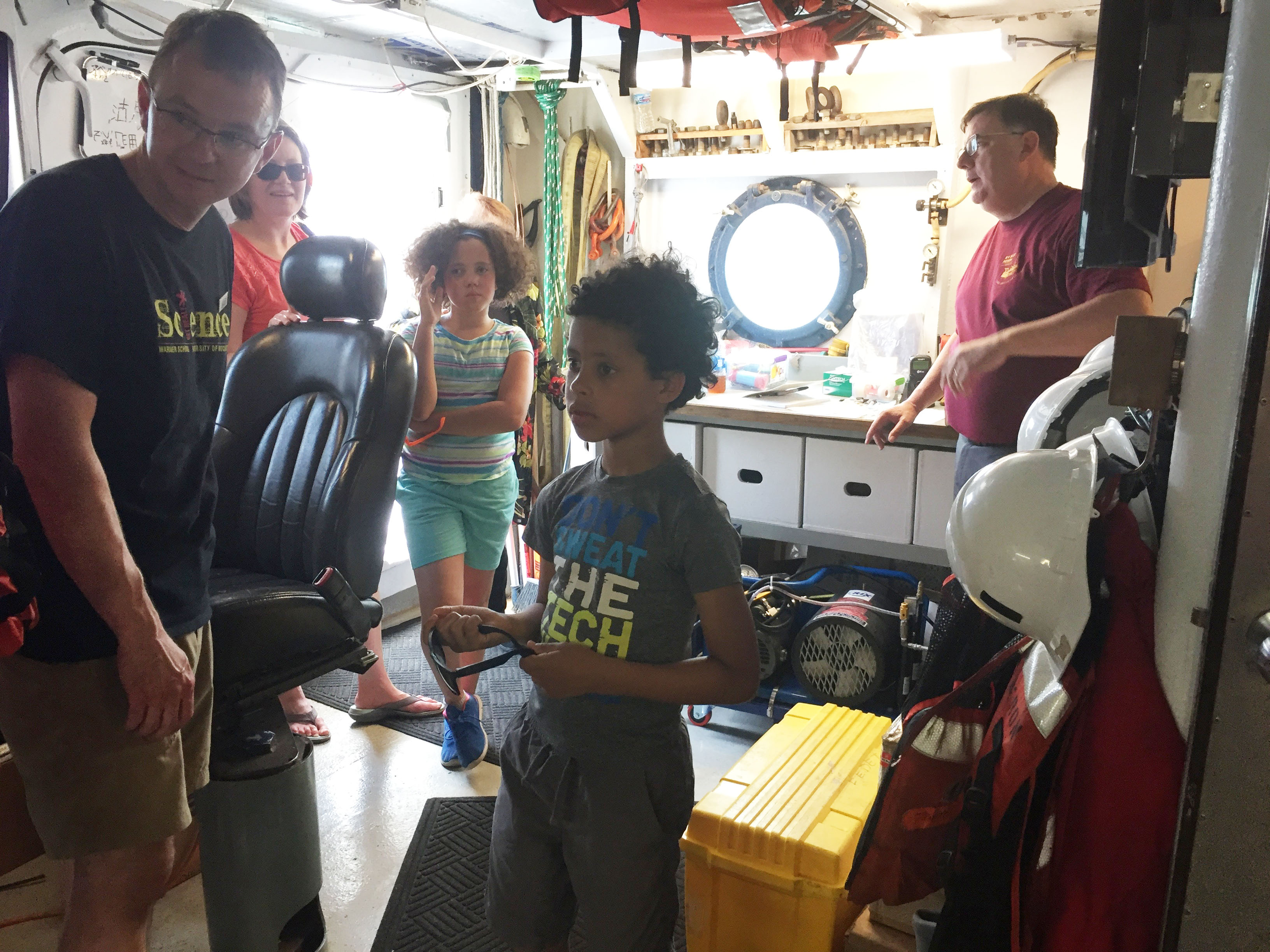 researchers shows kids around boat