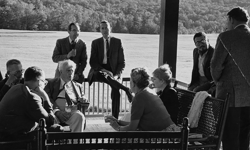 archival image of Bread Loaf conference writers, including poet RObert Frost, sitting outside near a lake