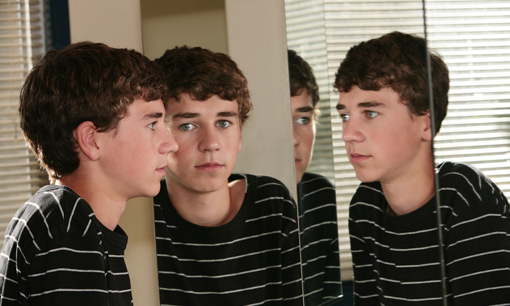 boy looking at multiple reflections of himself in mirrors