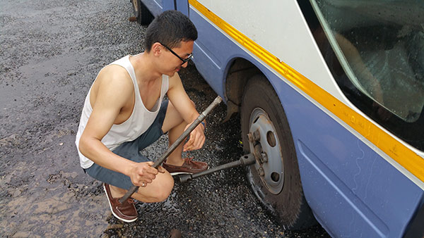 Jiacheng trying to change a tire