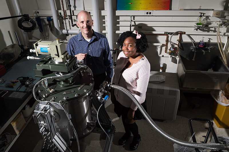 student and professor pose in lab