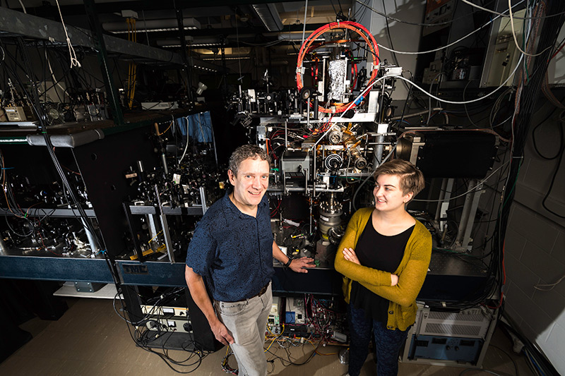 student and professor in lab surrounded by optics