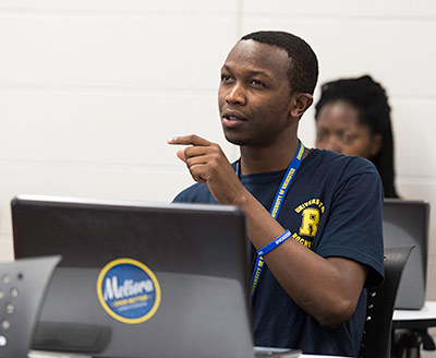 student sitting behind a computer with a MELIORA sticker