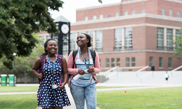 two students walking past the clock tower on campus
