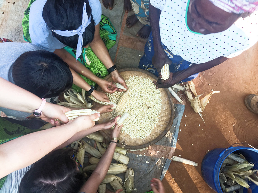 many hands around a bowl of corn