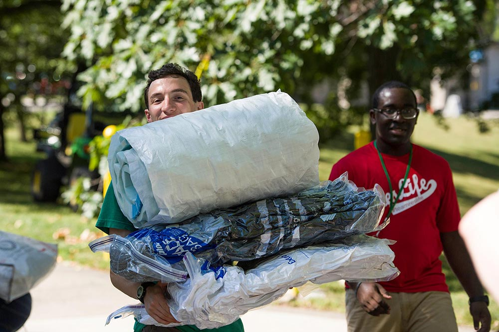 students carrying lots of stuff as they move into residence halls