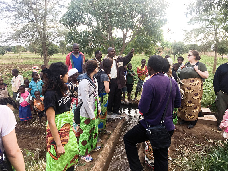 large group of students standing around an irrigation pipe