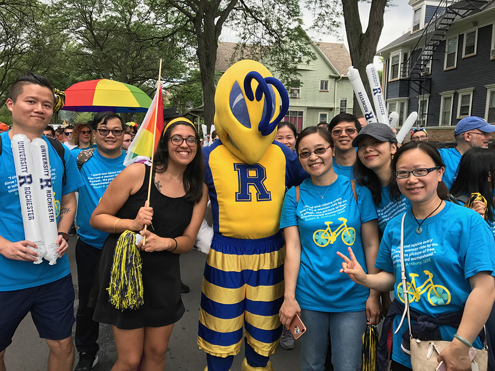 group of marchers in Pride Parade pose with the Rocky yellowjacket mascot