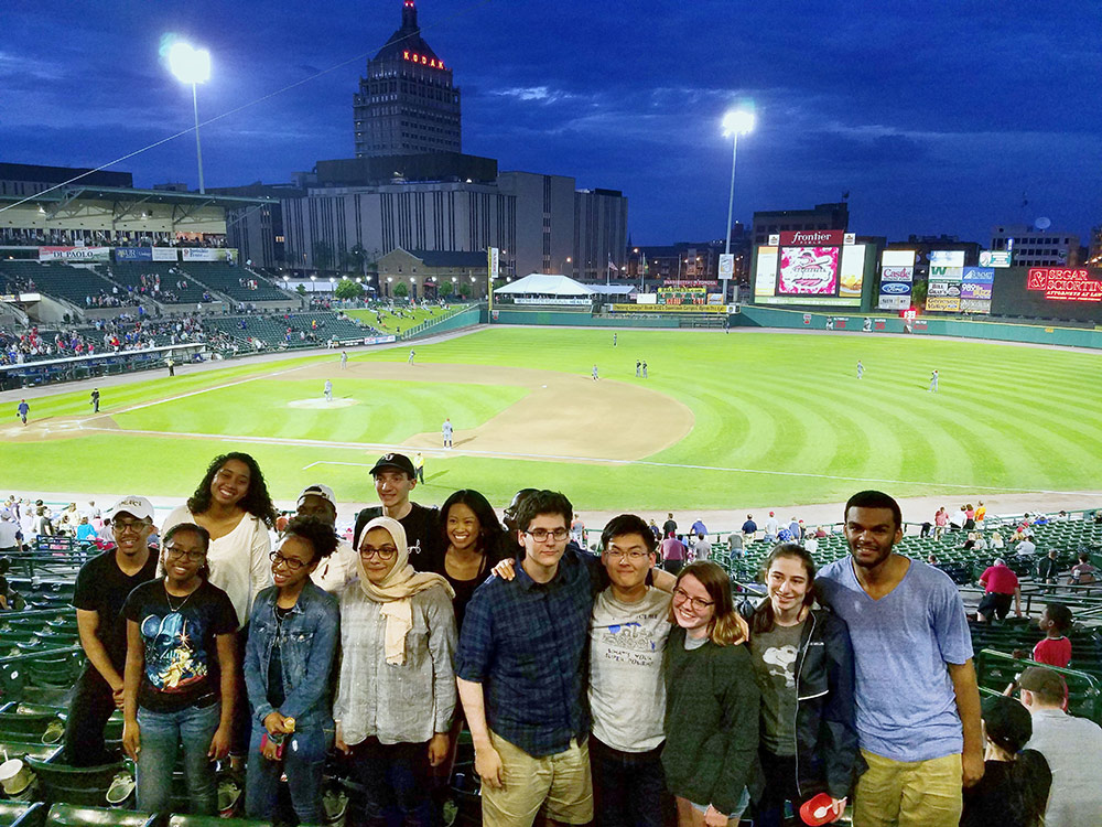 group of students pose for a photo a Frontier Field, with Kodak tower and Rochester skyline in background