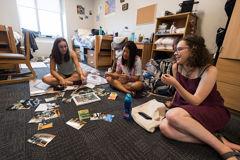 three students sitting on floor, looking at photos