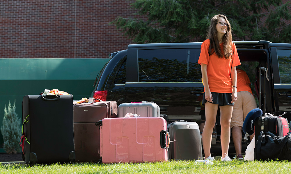 student standing next to car filled with luggage