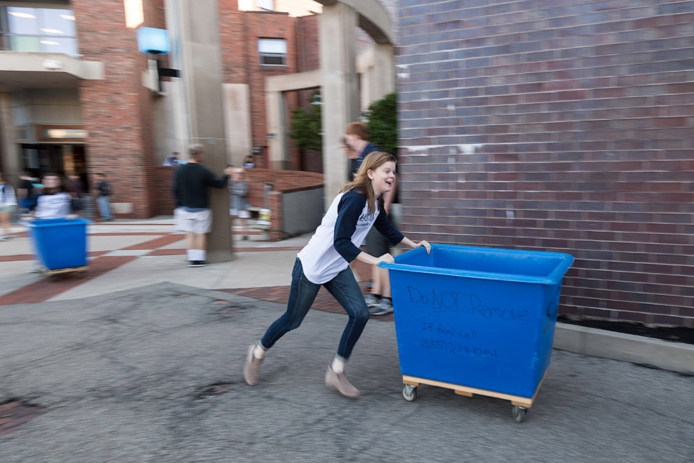 student running, pushing a large blue cart