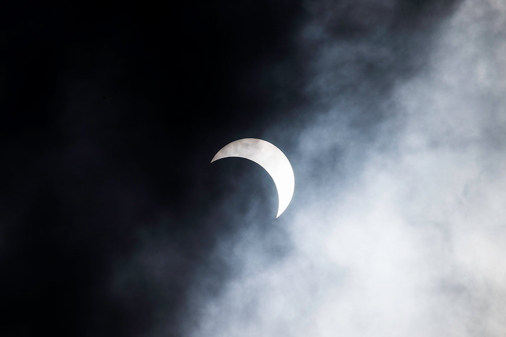 moon covering the sun, seen through clouds