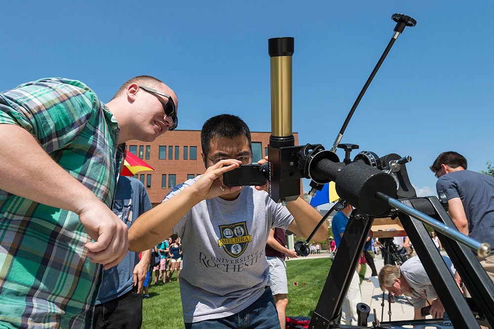 students with smartphones looking through a telescope