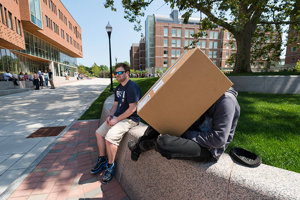 two students, one with his head inside a large cardboard box