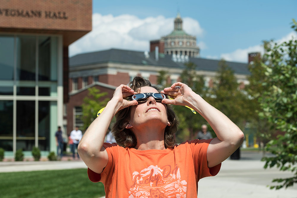 woman with eclipse glasses looking up