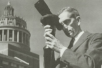 historical photo of Brian O'Brien using a telescope, with Rush Rhees Library in the background