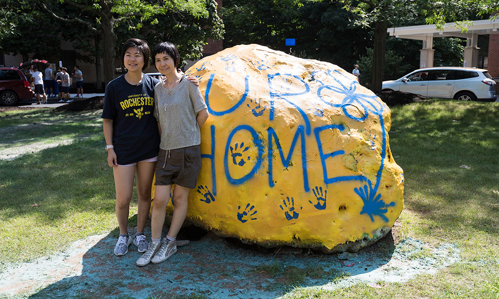 two people pose next to a rock painted with the words UR HOME