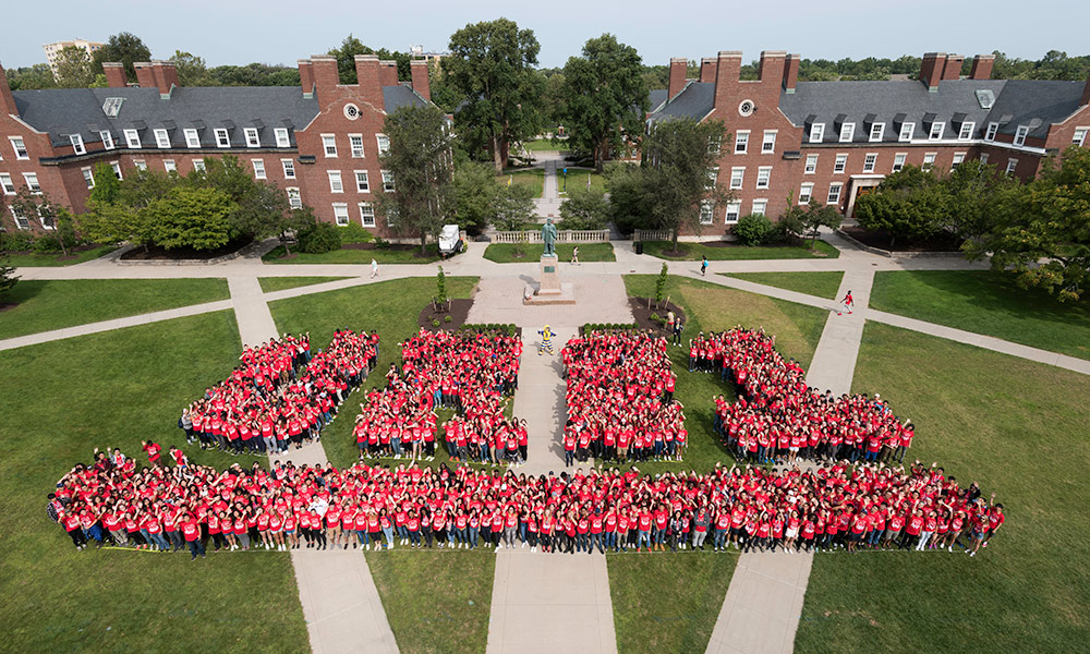 students wearing matching red t-shirts form the letters UR21