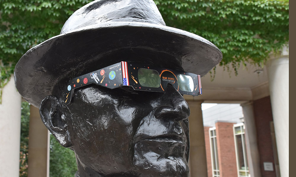 statue of George Eastman wearing solar eclipse glasses
