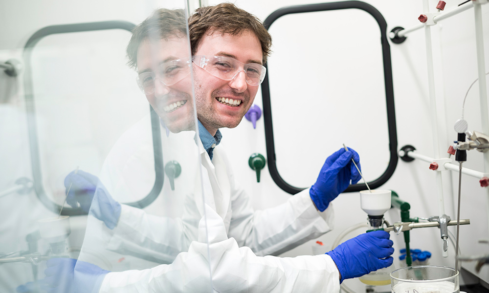 man smiles for a photo while working in a lab