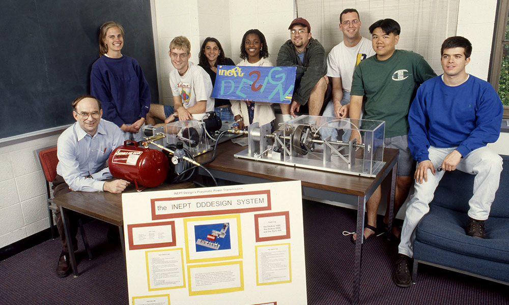 large group of students standing around a small red machine with their professor