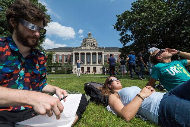 three people sitting on the quad, watching the eclipse