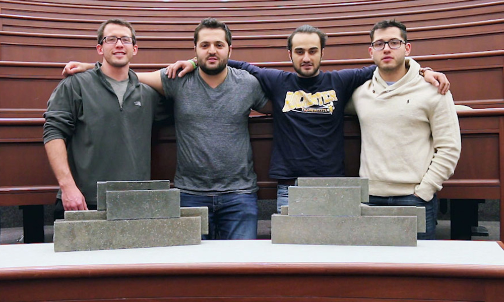 four team members pose behind a table covered in bricks