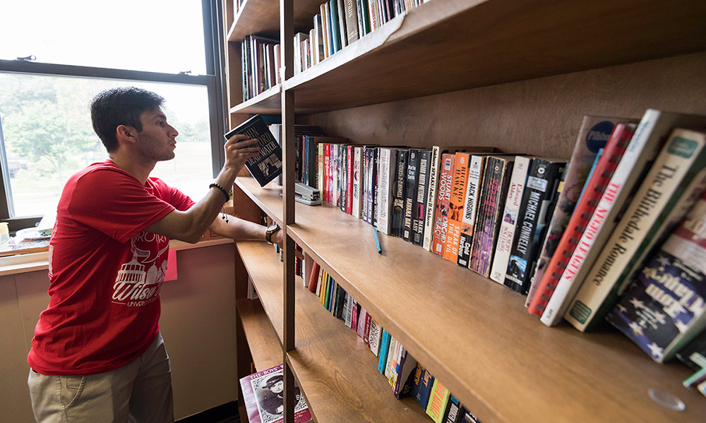 student placing books on a shelf
