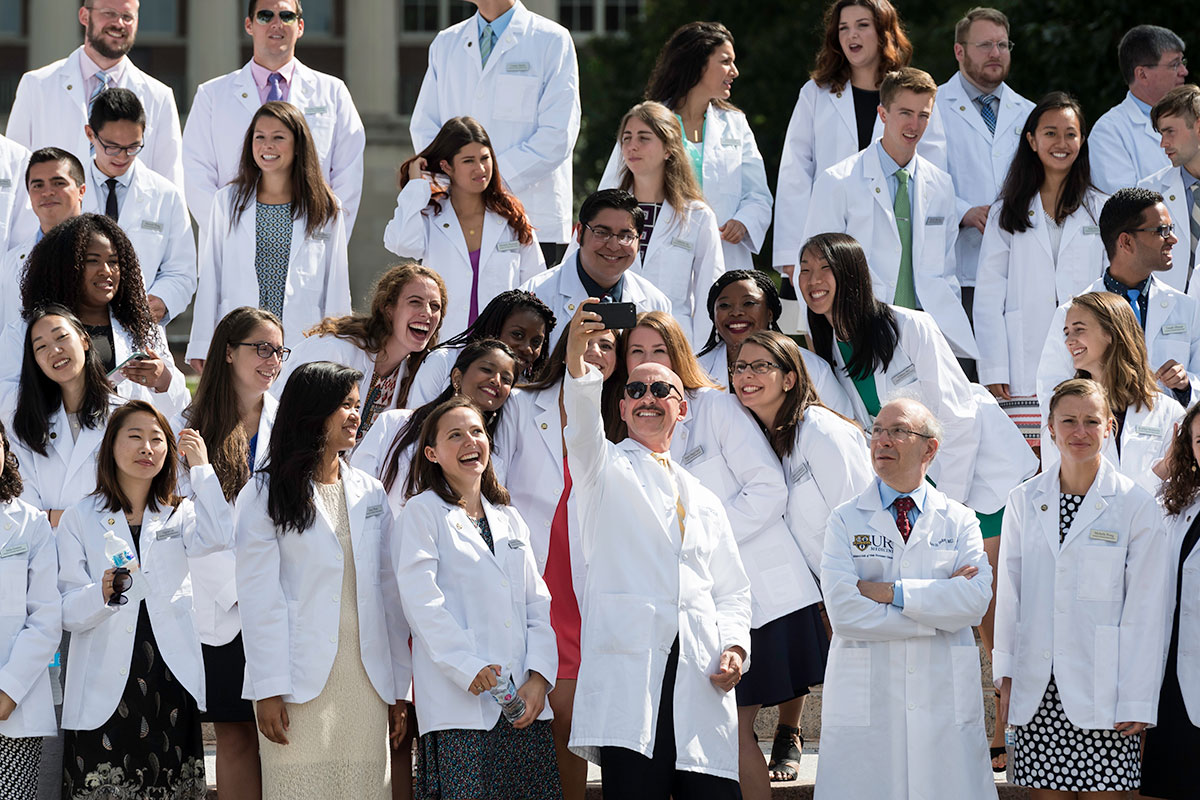 students taking selfie, all wearing white doctors coats