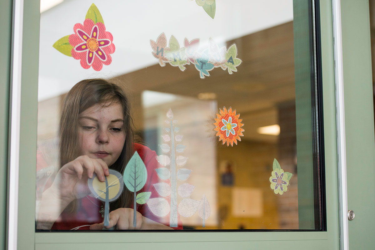 Student applying stickers of trees and flowers to a window