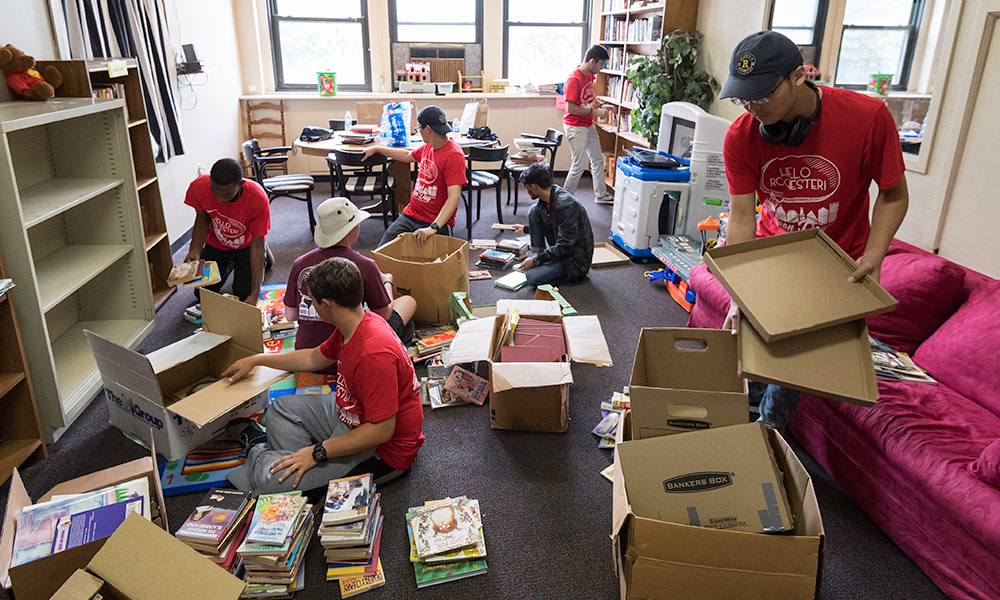 students organizing boxes of books in a classroom