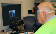 Man with therapeutic glasses stares at an image of an eye on a computer monitor