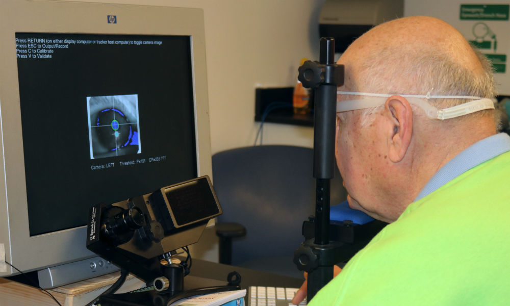 patient rests his chin and forehead on a device while looking at a screen
