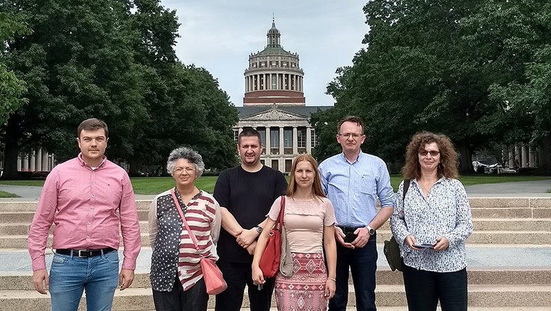 group photo of six people standing in front of library