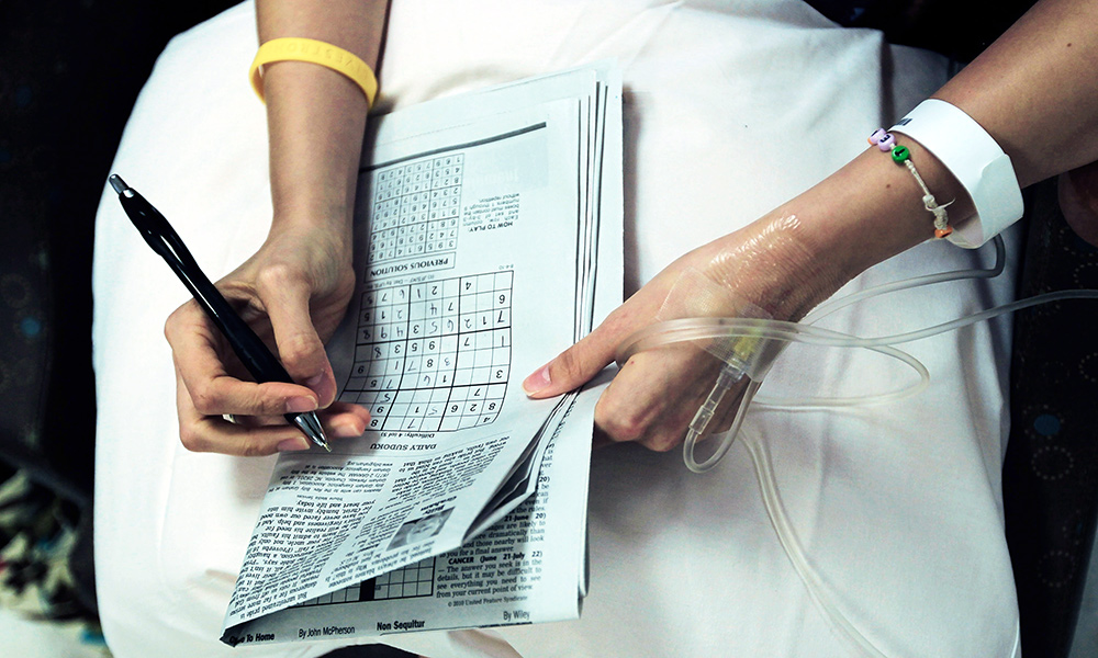 woman with an IV in her hand, working a crossword puzzle