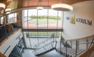 Sign reads BIG R ATRIUM, with the blue R for Rochester and with athletic fields visible out the window