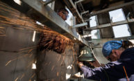sparks fly as workers use a grider on a bell