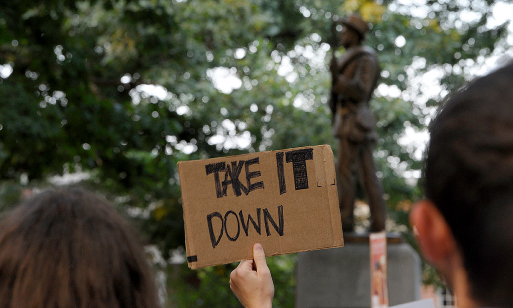 a confederate monument in the background with a person holding a sign that reads TAKE IT DOWN