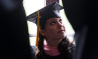 graduate at Eastman School of Music looks up while wearing cap and gown