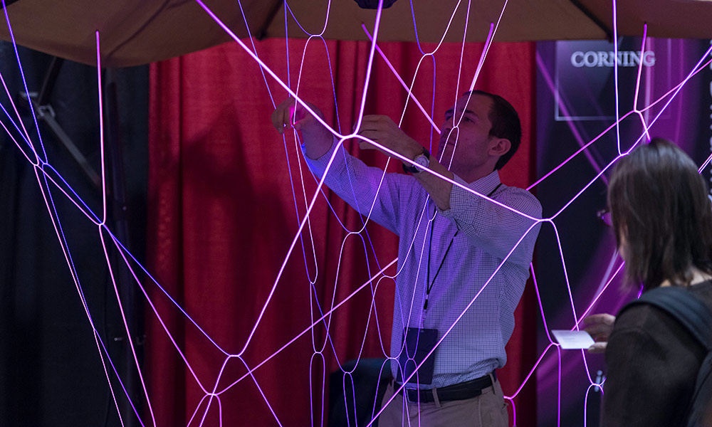 man surrounded by thin, colorful strands of light