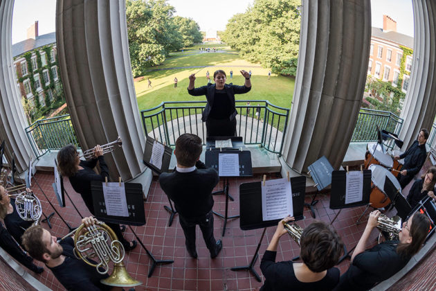conductor raises arms and faces musicians playing on a balcony