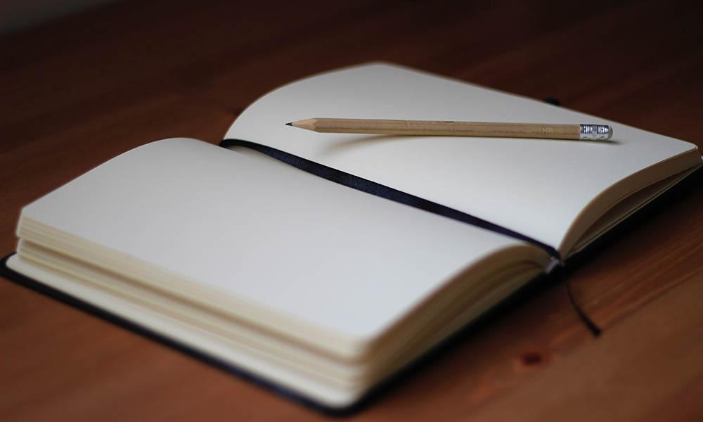 A pencil lies atop an open, blank book