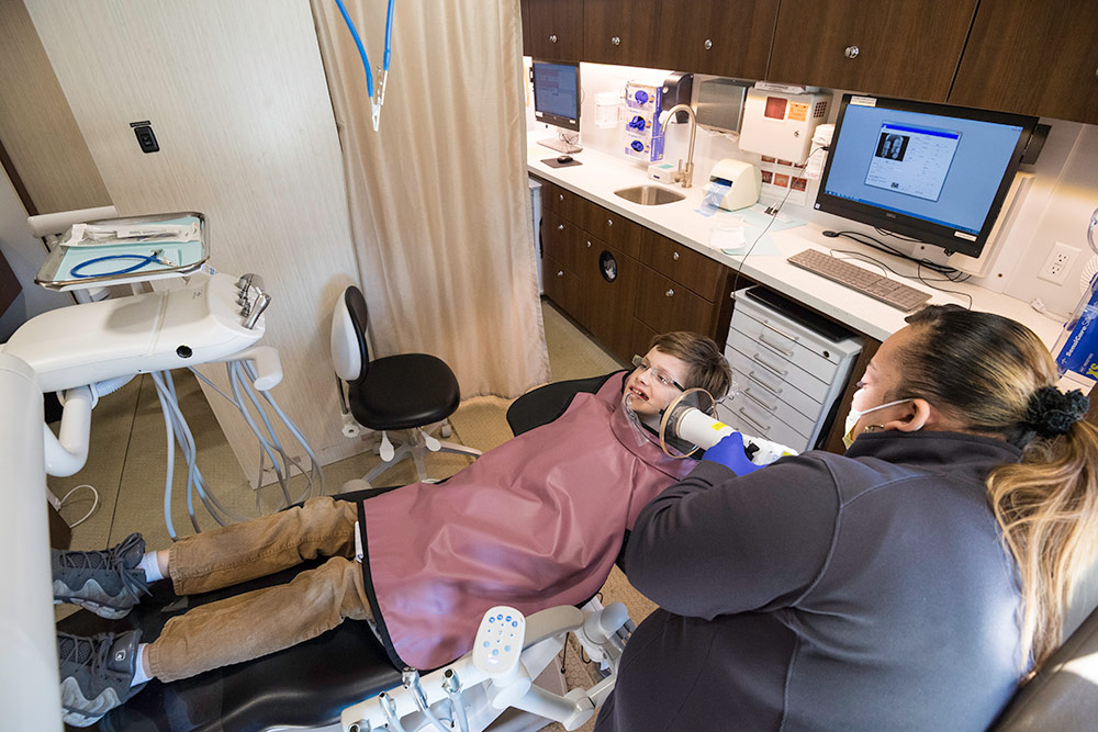 overhead view of dental technician examining boy in a dentist chair