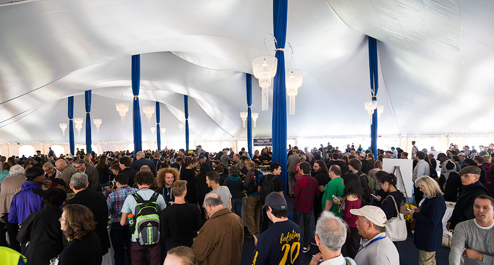 crowds in a tent with chandeliers
