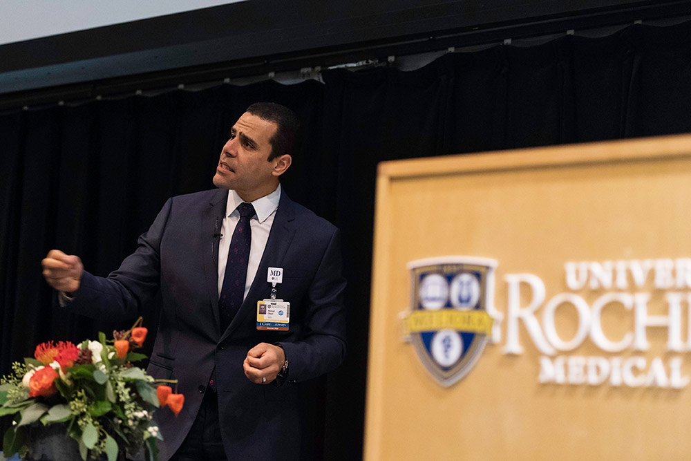 man giving presentation near UR Medicine podium
