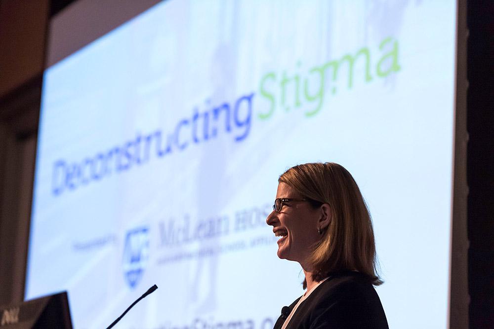 smiling woman in front of presentation slide reading DeconstructingStigma