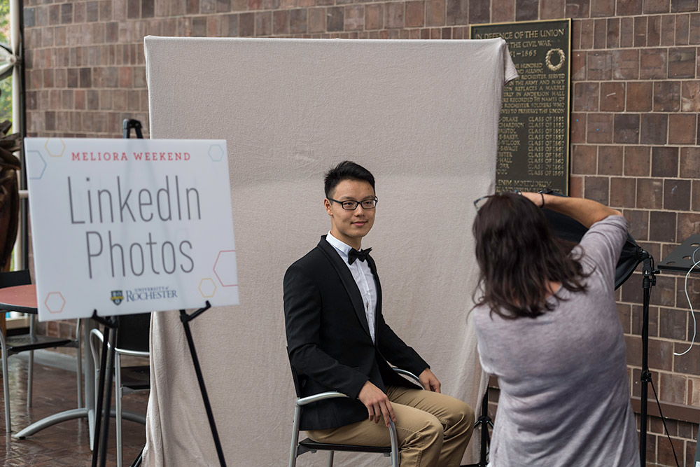 photographer takes a photo of a young man in a bow tie)