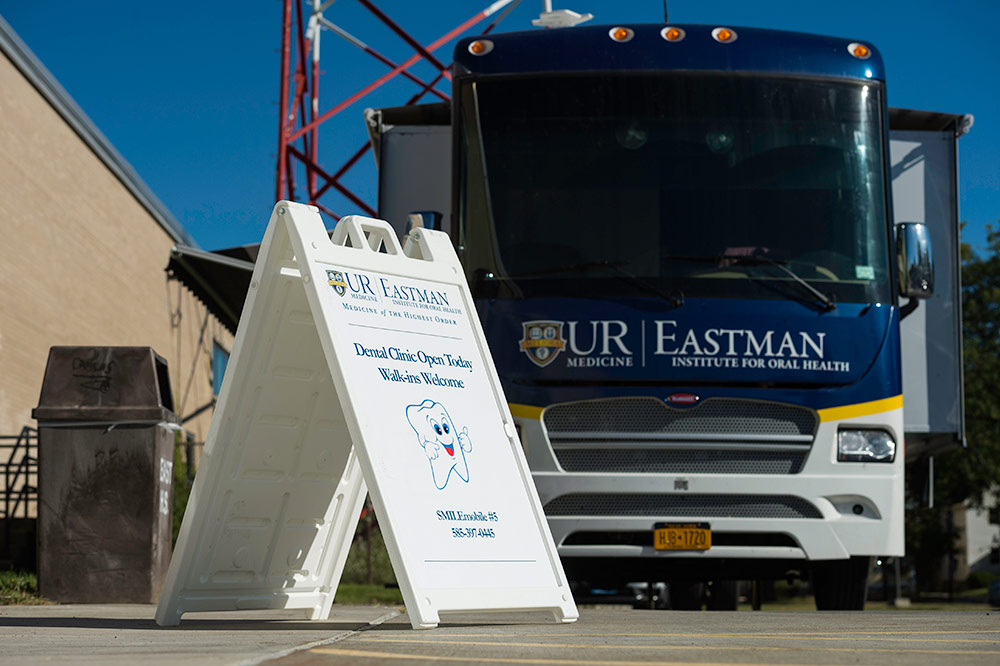 sign for smile mobile and UR Eastman bus outside a school